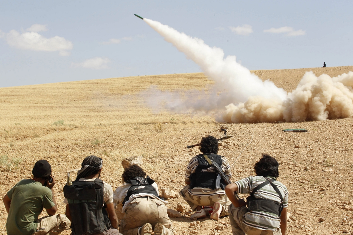 Free Syrian Army fighters fire a rocket towards forces loyal to Syria's President Bashar al-Assad in Hama countryside