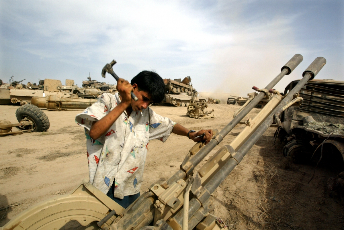 An Iraqi man recovers metal parts from an anti-aircraft gun in a wreckage dump on the outskirts of Baghdad