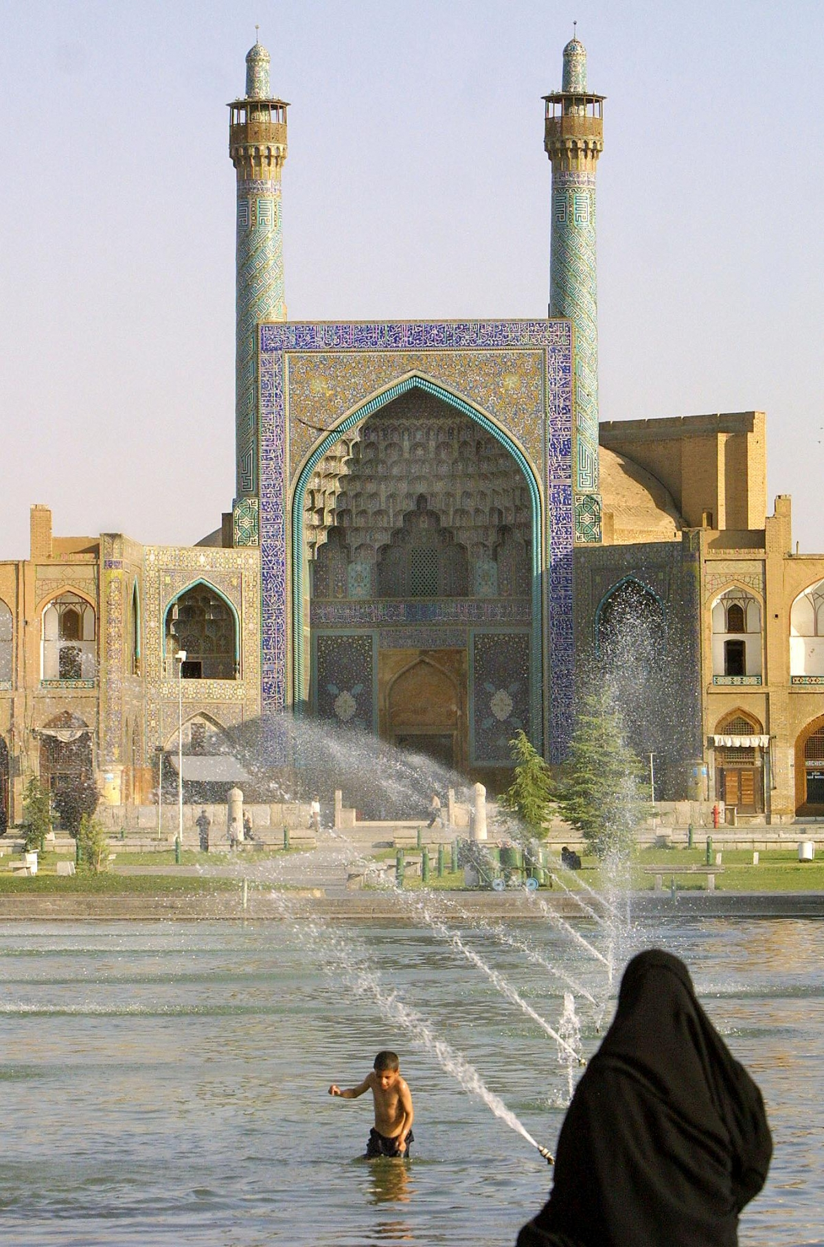 An Iranian woman looks at a boy swiming in the pool of Imam square (royal square) as the historic Imam mosque built in 1638 is seen in the background in Isfahan