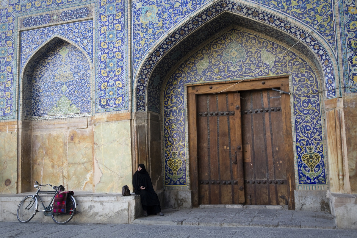 An Iranian woman observes prayers while sitting outside the Imam Khomeini mosque at the historical Naqsh-e Jahan Square in Isfahan (Getty)