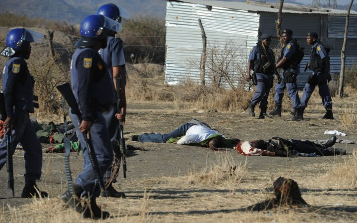 Police stand over the bodies of dead protesters in Marikana, 2012. (Getty)
