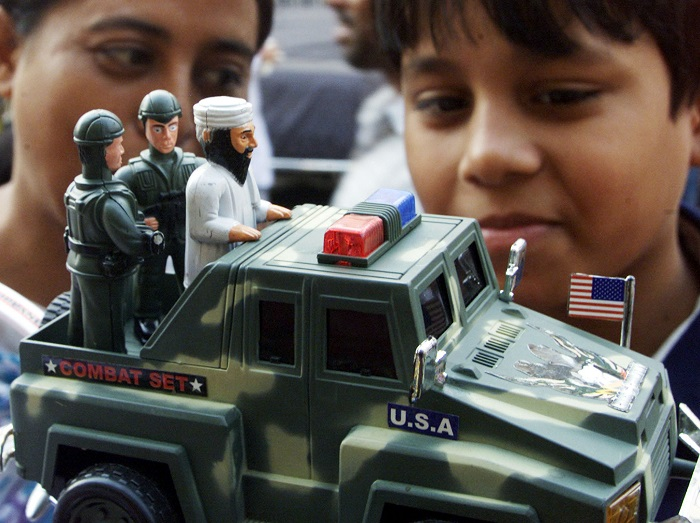 Bangladeshi children play with a toy depicting Osama bin Laden riding on the back of a jeep after being arrested by the US military.