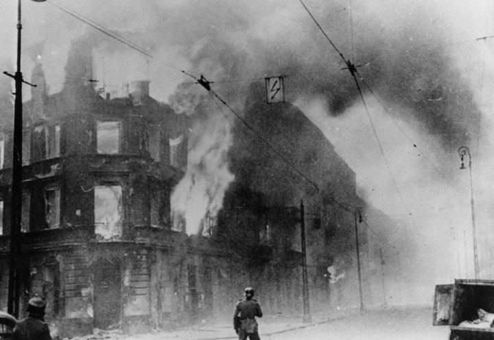 A building burns during the first Warsaw uprising in 1943 (Getty)