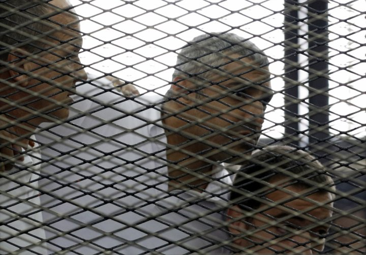 Peter Greste, Mohamed Fahmy and Baher Mohamed (L to R) listen to a ruling at a court in Cairo