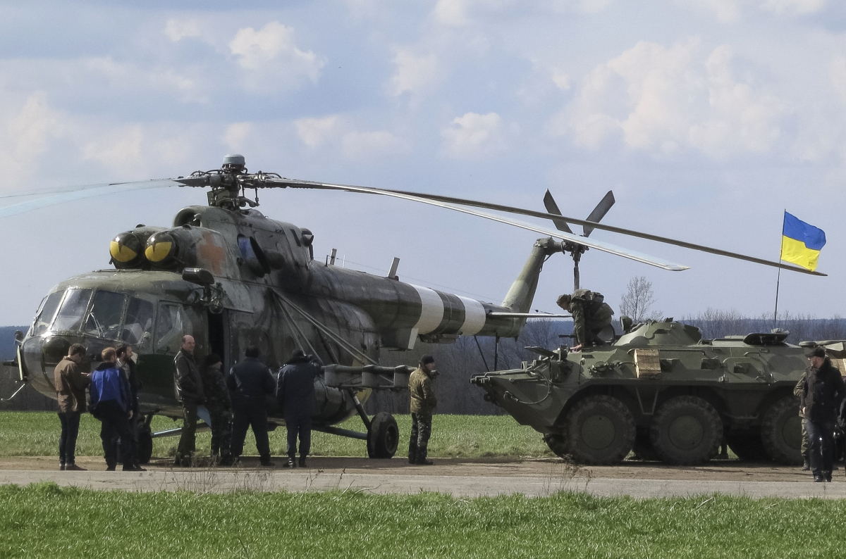 Ukrainian soldiers are seen near a MI-8 military helicopter