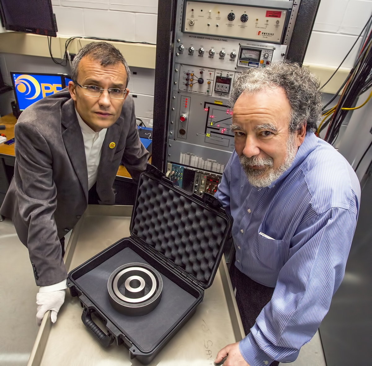 Physicists Alexander Glaser, left, and Robert Goldston, display the non-nuclear test object that will serve as a target in their research.