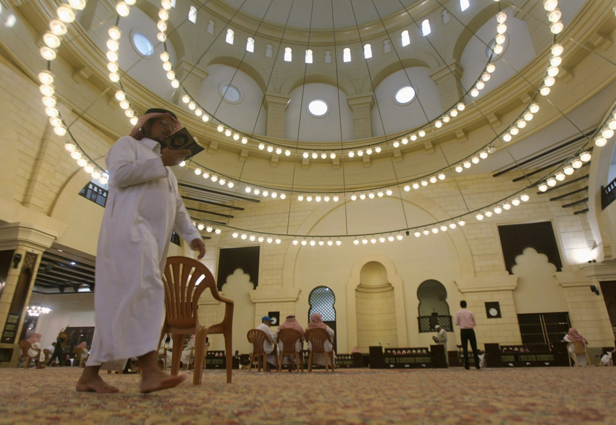 A Muslim man walks past as he reads the Koran at the Al-Rajhi mosque east of Riyadh