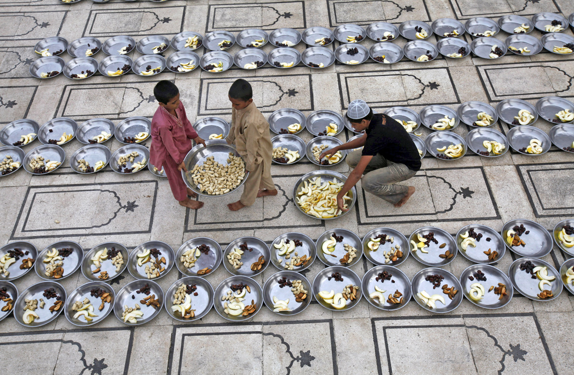 Volunteers prepare plates of food at the mosque for Iftar, the evening meal