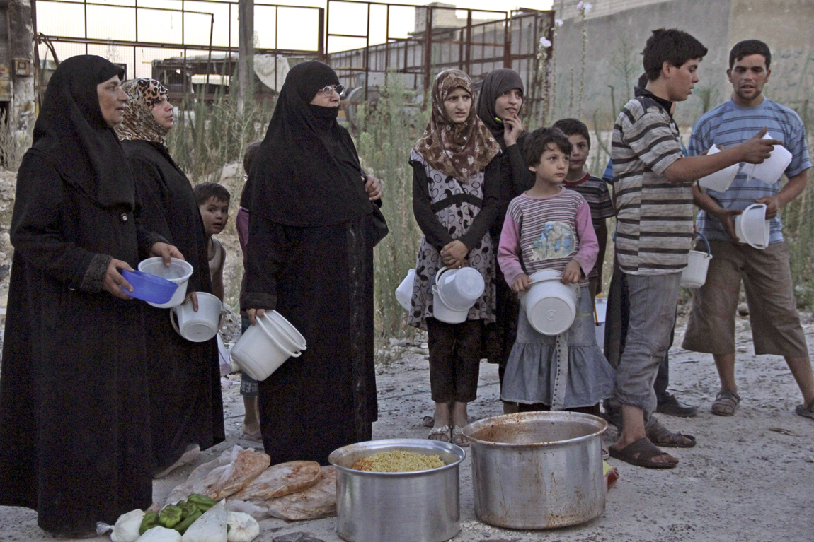 People wait for the time for the Iftar meal to break their fast in Aleppo, Syria