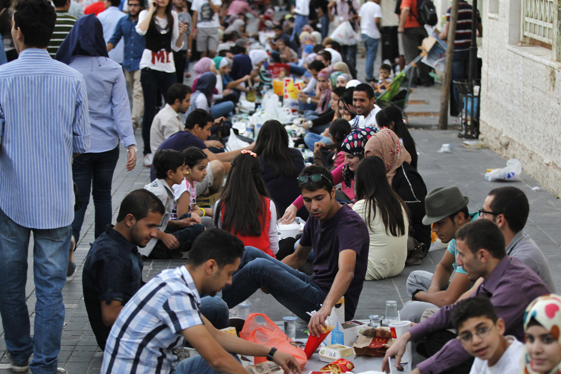 Hundreds gather on a street to break their fast together in Amman after being contacted through social media