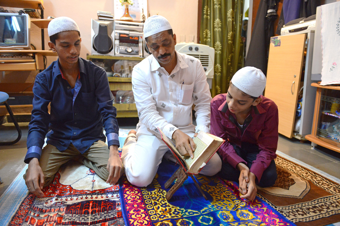 An Indian Muslim family reads the Quran after breaking their fast at their home in Hyderabad, India
