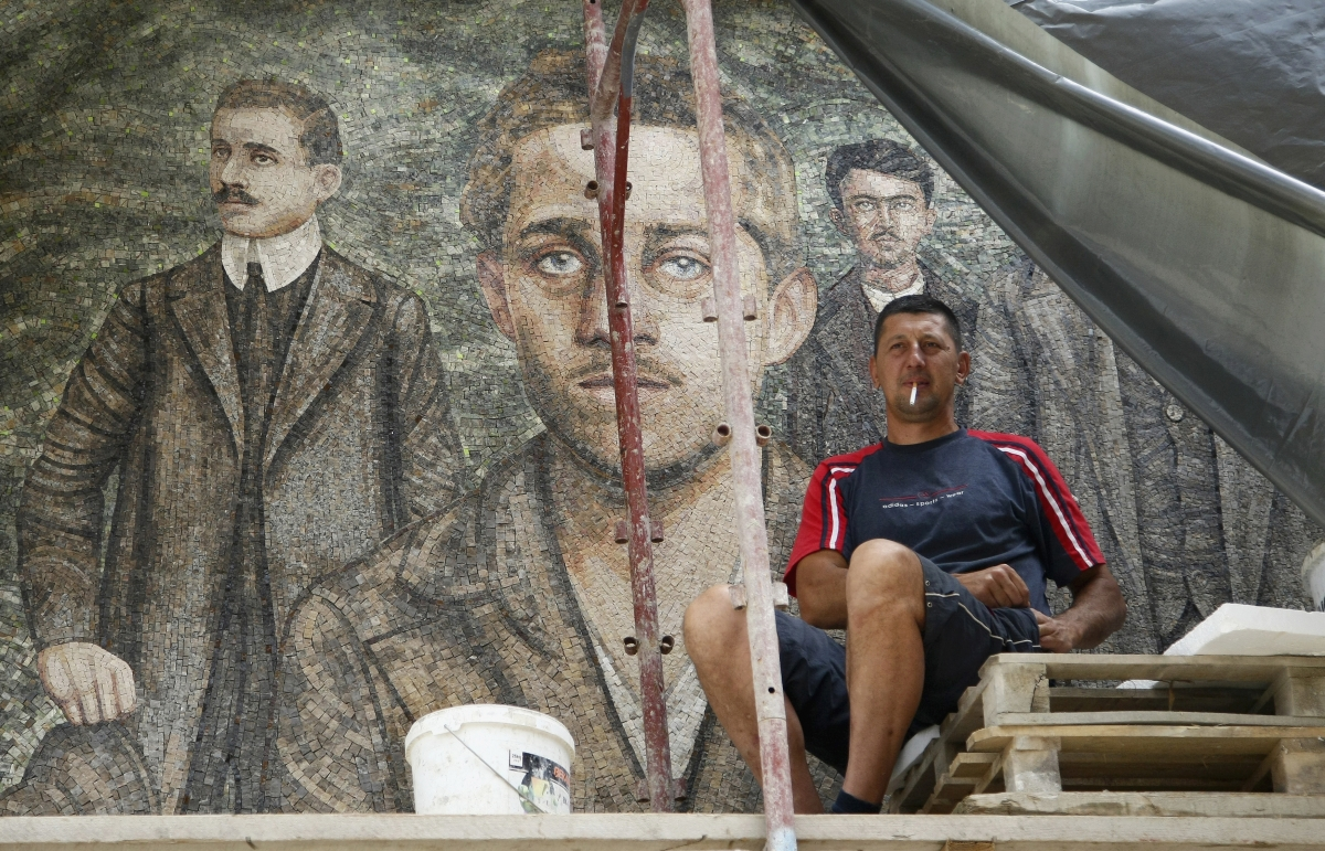 A worker smokes a cigarette in front of a mosaic with image of Gavrilo Princip, in Andricgrad village near Visegrad
