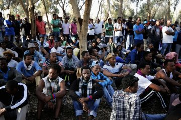 African asylum seekers gather for a morning meeting during an overnight protest after leaving Holot open detention centre in southern Israel's Negev desert
