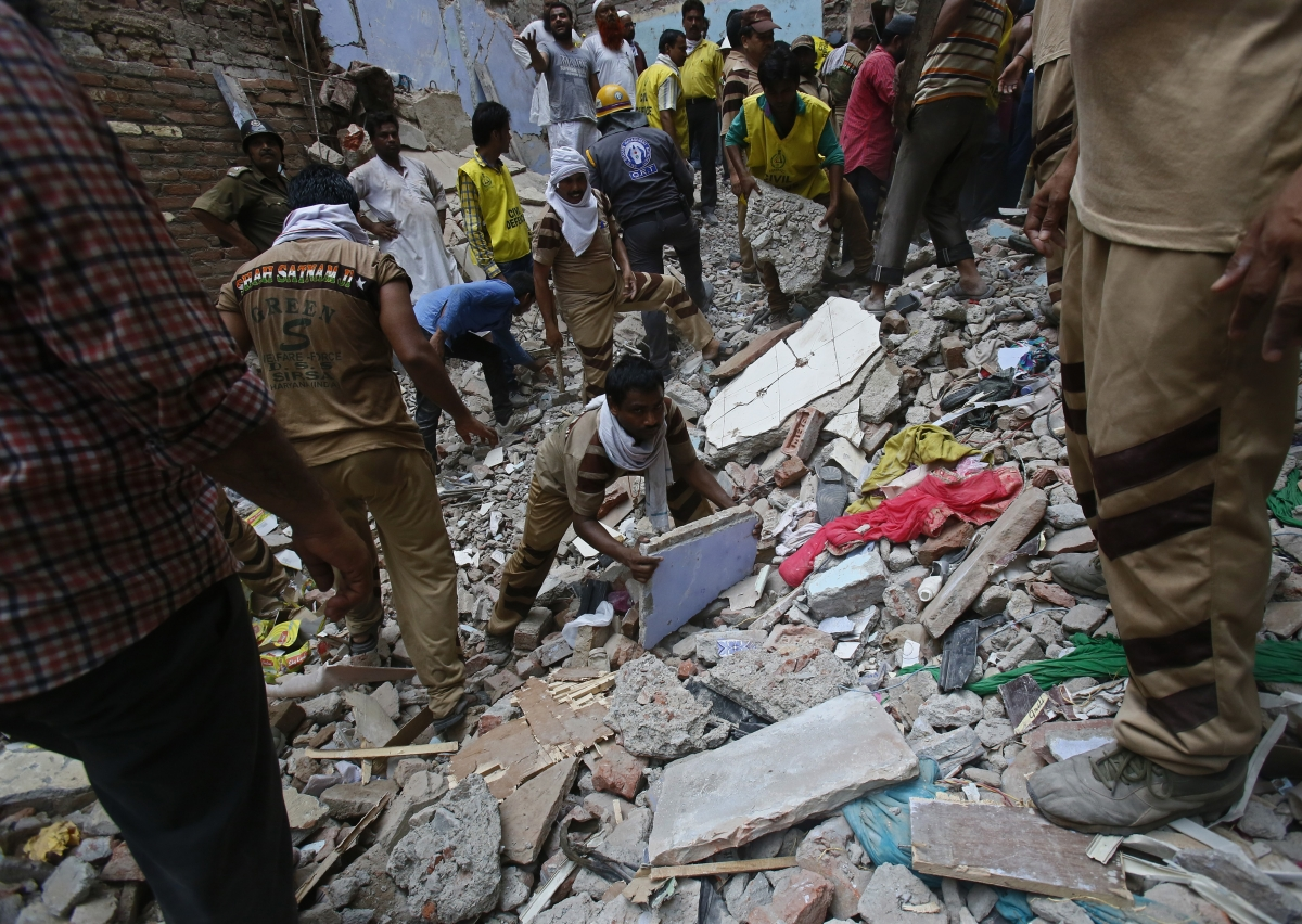 Rescue workers clear the debris from the site of a collapsed building in New Delhi