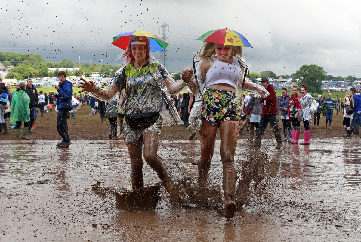 Happy despite the mud. Festival goers splash through puddles at the Glastonbury music festival
