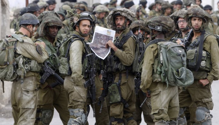 Israeli soldiers take part in an operation to locate three Israeli teens