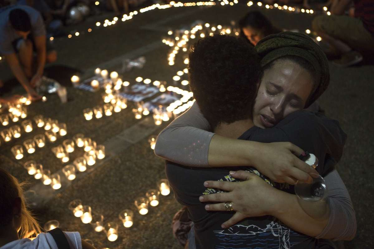 sraeli women hug each other as people light candles in Tel Aviv's Rabin Square as they mourn the death of three teenagers who were abducted,