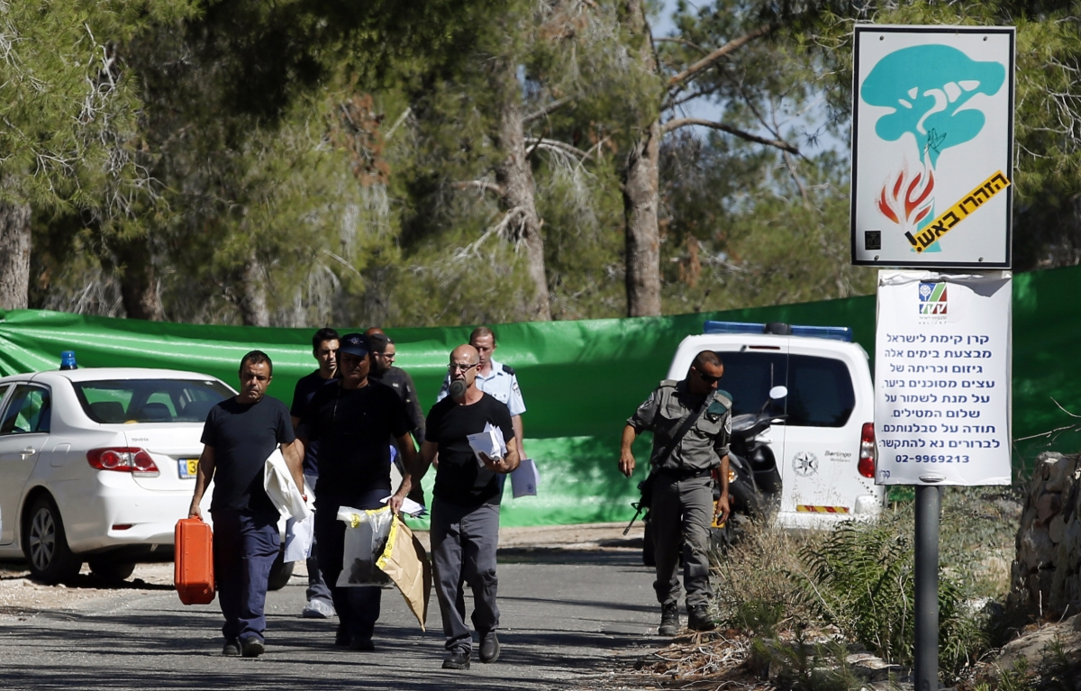 Israeli police crime scene investigators carry evidence from the scene where a body was found in the Jerusalem Forest