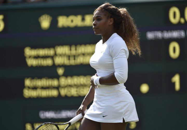 Serena Williams of the U.S. holds her stomach before retiring from her women's doubles tennis match with Venus Williams of the U.S. against Kristina Barrois of Germany and Stefanie Voegele of Switzerland at the Wimbledon Tennis Championships, in London J