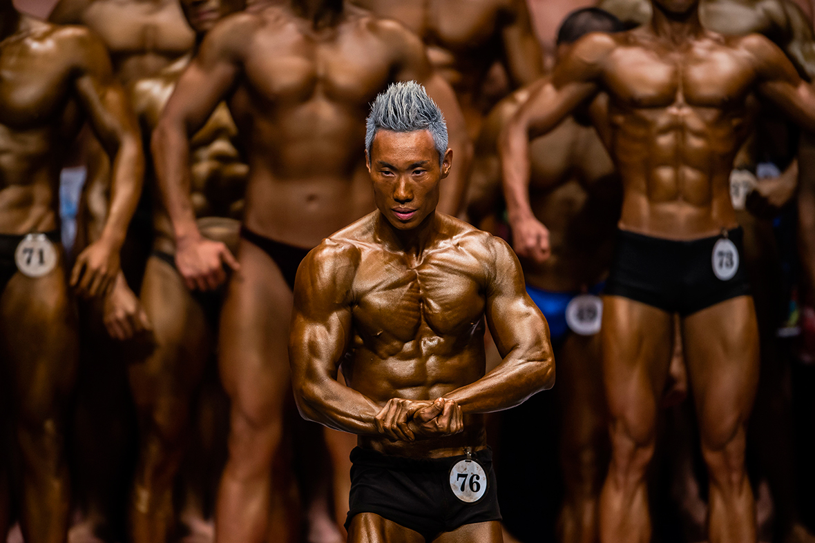 Bodybuilders flex muscles on stage during the Hong Kong Bodybuilding Championship