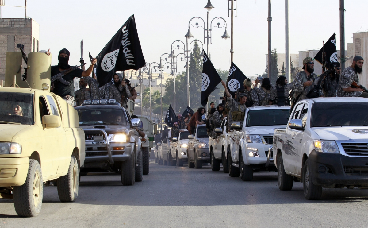 Islamic State fighters parade on military vehicles along the streets of a northern Raqqa province in Syria