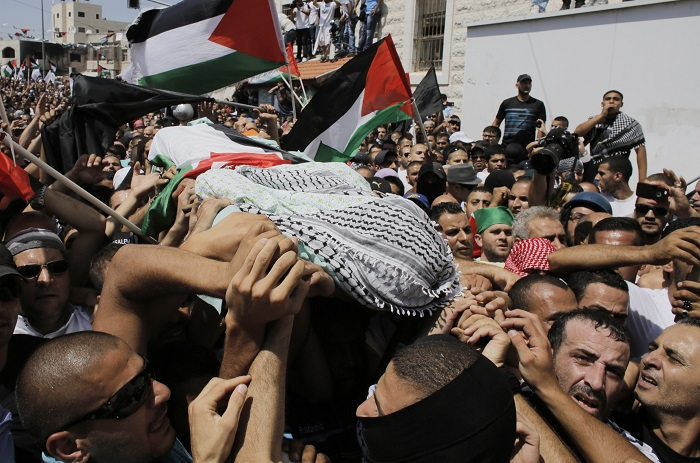 Palestinians carry the body of Mohammed Abu Khudair during his funeral in Shuafat, an Arab suburb of Jerusalem on 4 July 2014.