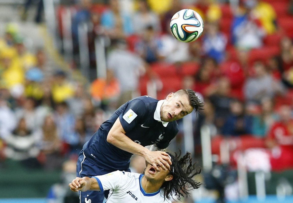 Don't look now: France's Mathieu Debuchy fights with Roger Espinoza of Honduras for the ball during their 2014 World Cup Group E soccer match at the Beira-Rio stadium in Porto Alegre