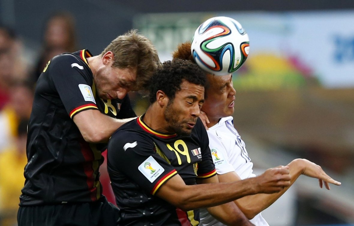 Doing the hand jive: South Korea's Kim Shin-wook (R) fights for the ball with Belgium's Nicolas Lombaerts (L) and teammate Moussa Dembele during their 2014 World Cup Group H soccer match at the Corinthians arena in Sao Paulo