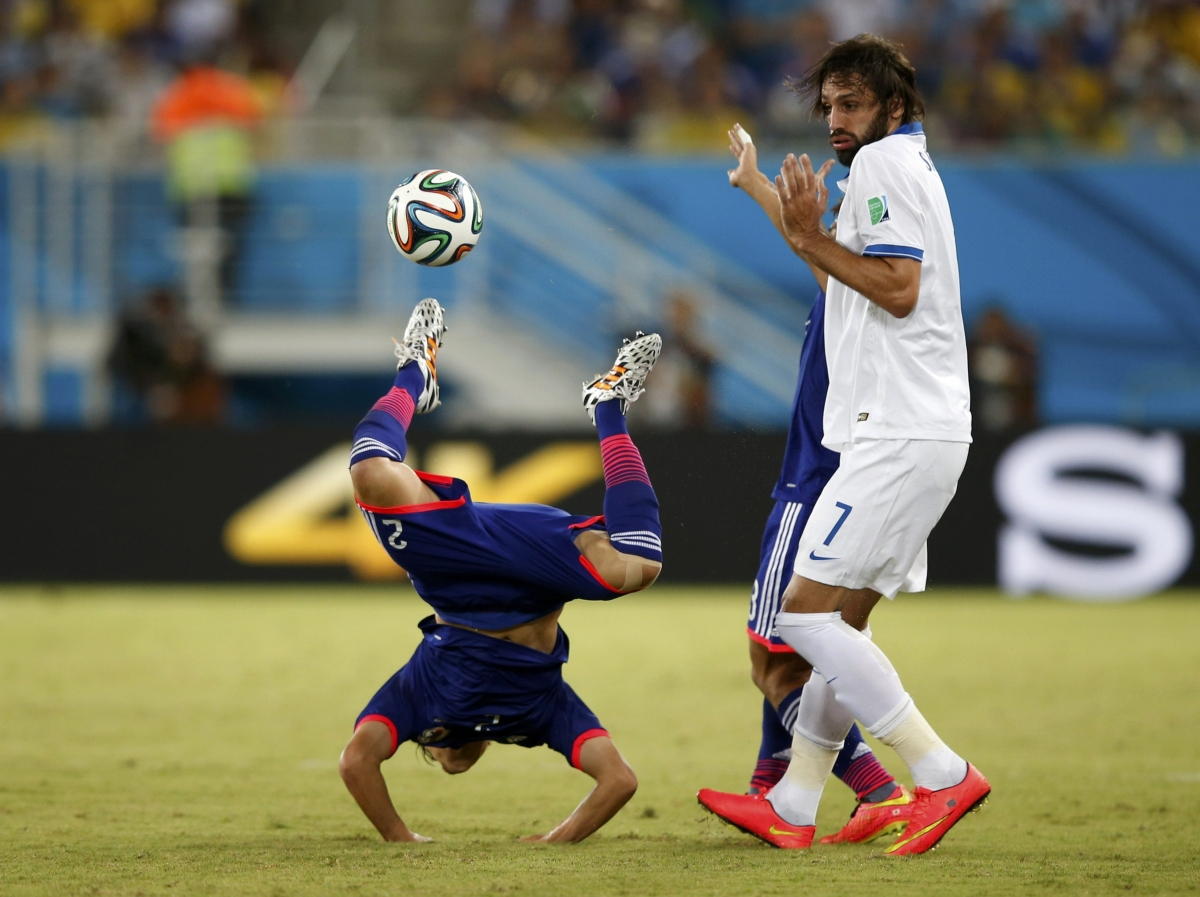 I didn't touch him, says Greece's Giorgios Samaras, after committing a foul against Japan's Atsuto Uchida (L)