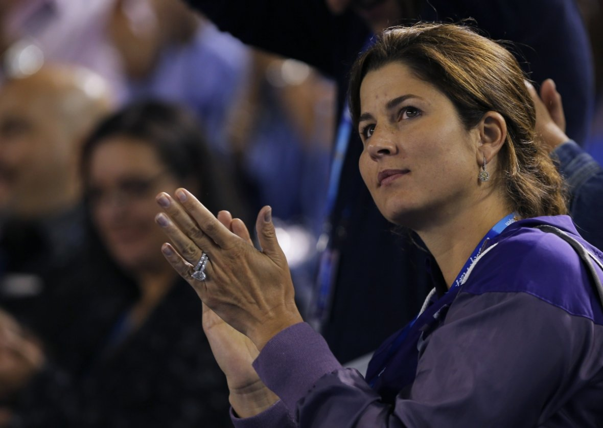 Mirka Federer, wife of Roger Federer of Switzerland, applauds as he gives an interview after he defeated Jo-Wilfried Tsonga of France in their men's singles quarter-final match at the Australian Open tennis tournament