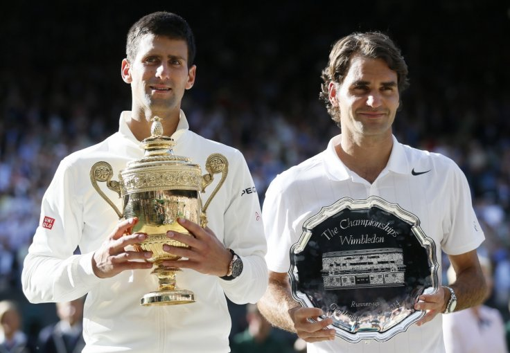 Novak Djokovic of Serbia holds the winner's trophy after defeating Roger Federer (R) of Switzerland, holding the runner-up's trophy, in their men's singles finals tennis match on Centre Court at the Wimbledon Tennis Championships in London July 6, 2014