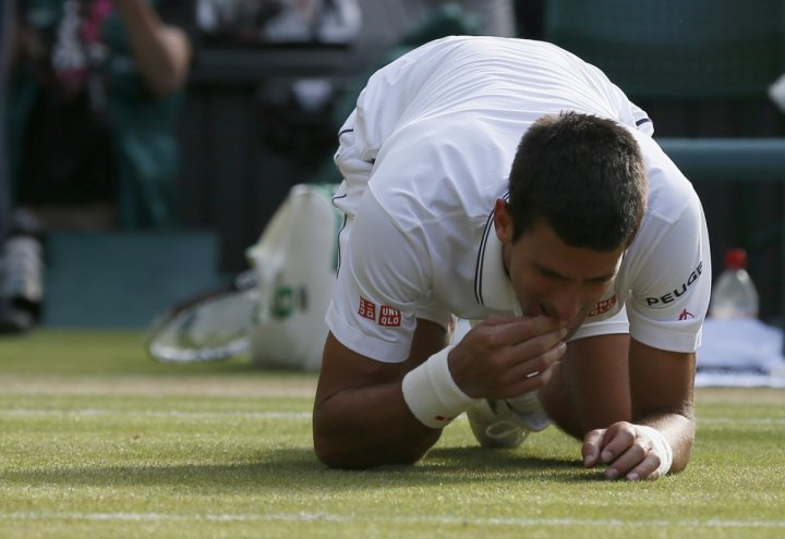 Novak Djokovic of Serbia eats some grass after defeating Roger Federer of Switzerland in their men's singles final tennis match at the Wimbledon Tennis Championships, in London July 6, 2014.