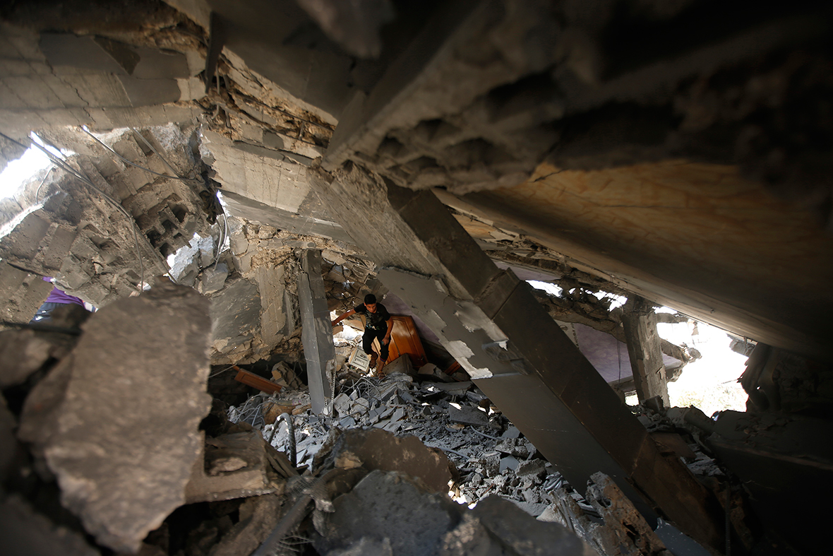 A Palestinian walks through the rubble of a house that was destroyed in an Israeli air strike, in the northern Gaza StripReuters