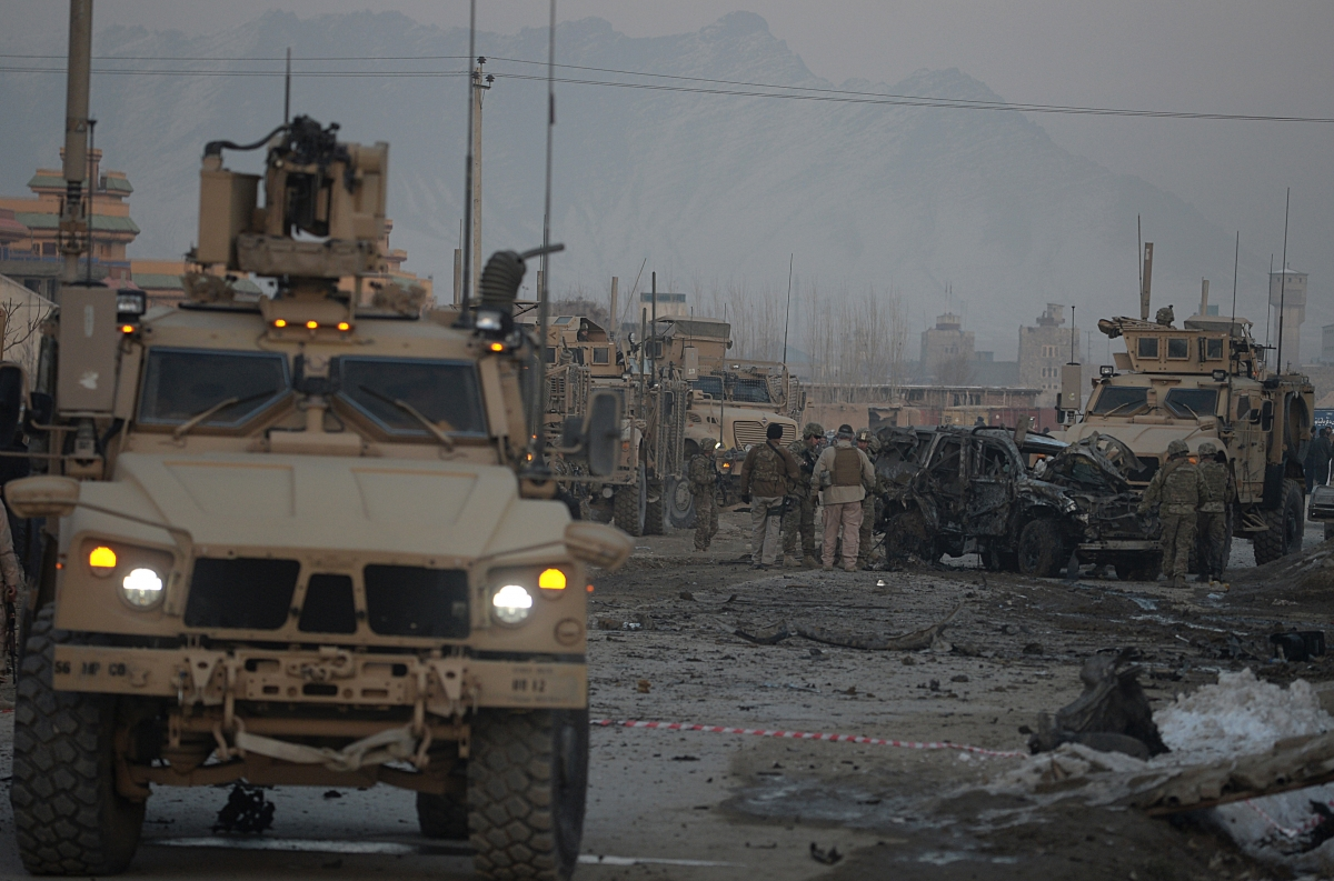 US soldiers examine a damaged vehicle at the site of a car bomb in Kabul