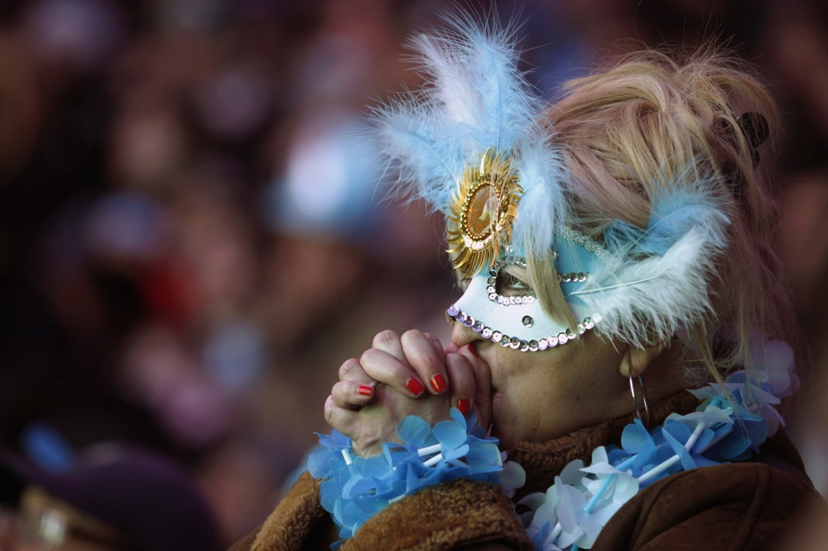 A masked fan holds her breath and prays for Argentina to beat Germany