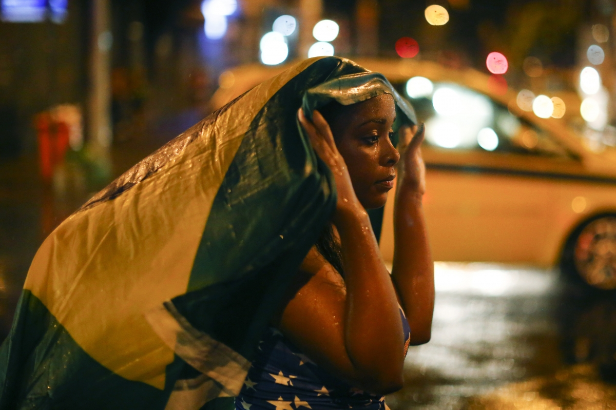 Drowning in tears: A Brazil fan walks in the rain after watching a broadcast of her team's loss against Germany