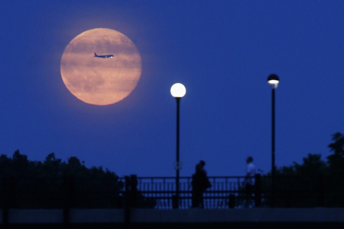 A plane passes in front of a Supermoon rising over the Rideau Canal in Ottawa, Canada