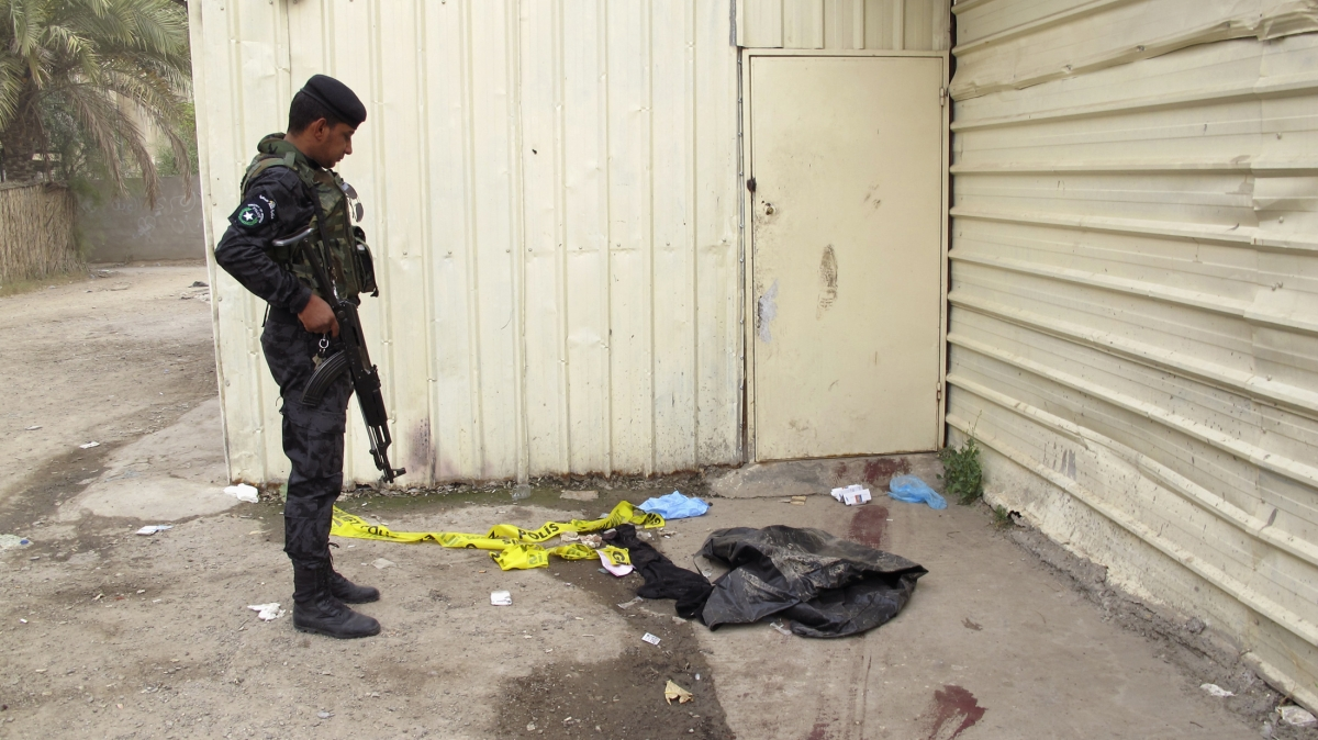 An Iraqi policeman looks at blood marks on the ground near an apartment building where a shooting occurred, in Baghdad (Reuters)