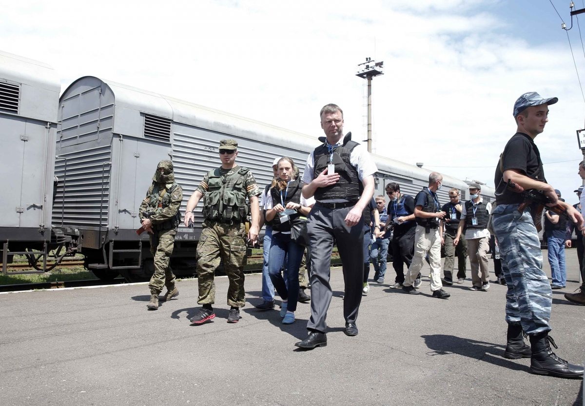 OCSE inspectors by the train carriages containing the victims of the MH17 crash. (Reuters)