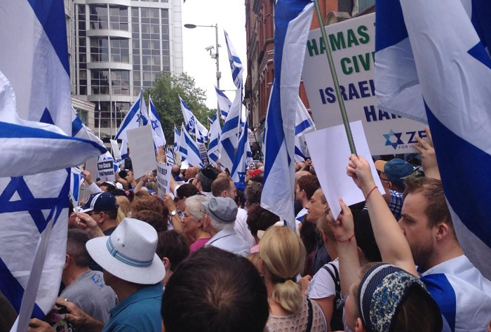 Protesters wave Israeli flags and pro-Israel placards at the demonstration in Kensington, west London.