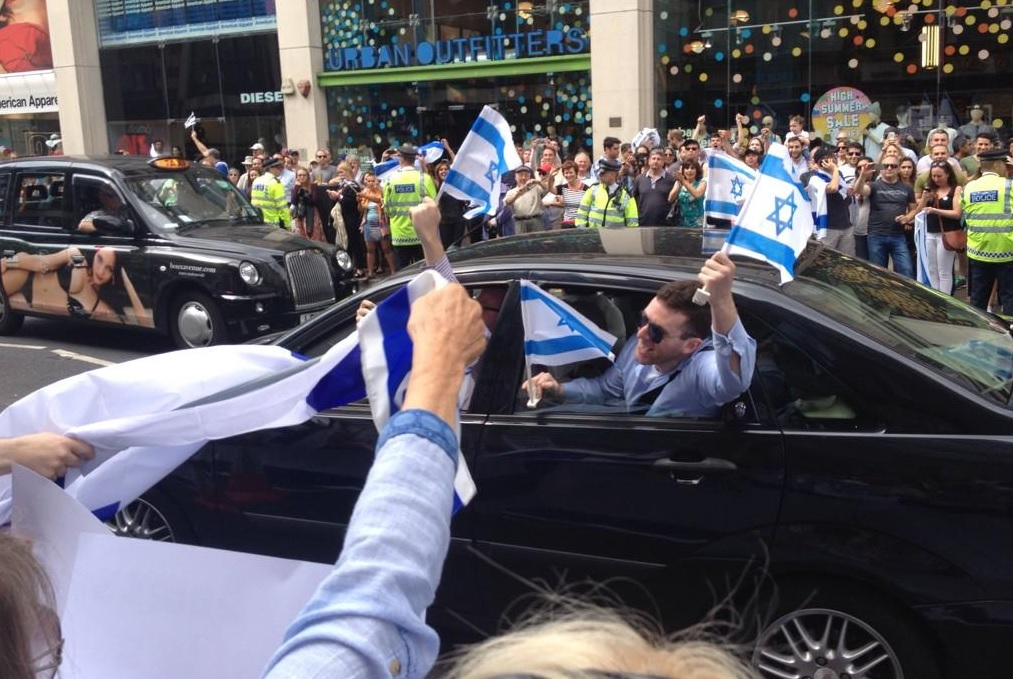 Protesters wave Israeli flags from a passing car at Sunday's pro-Israel demonstration.