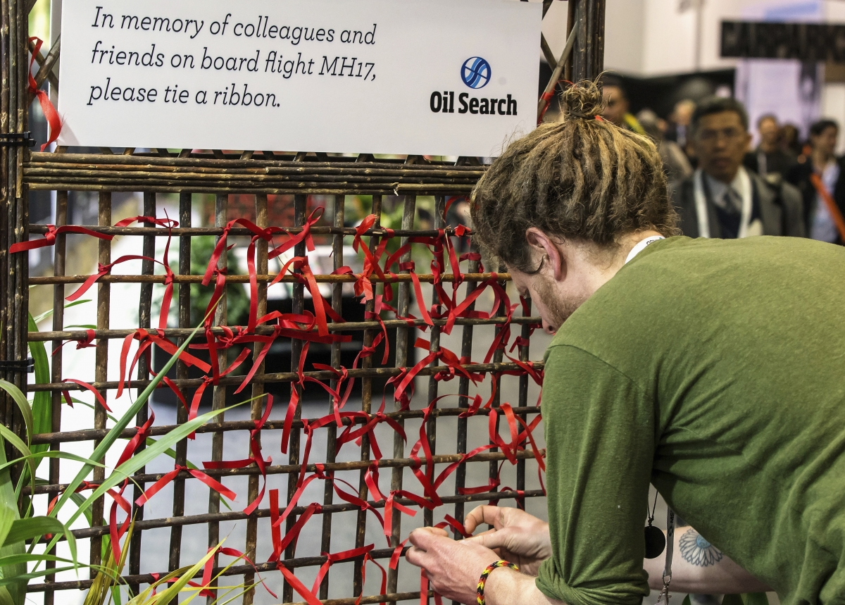 A delegate of the 20th International AIDS Conference ties a red ribbon to a memorial board as a tribute to colleagues killed in the Malaysia Airlines flight MH17, in Melbourne July 20, 2014 .