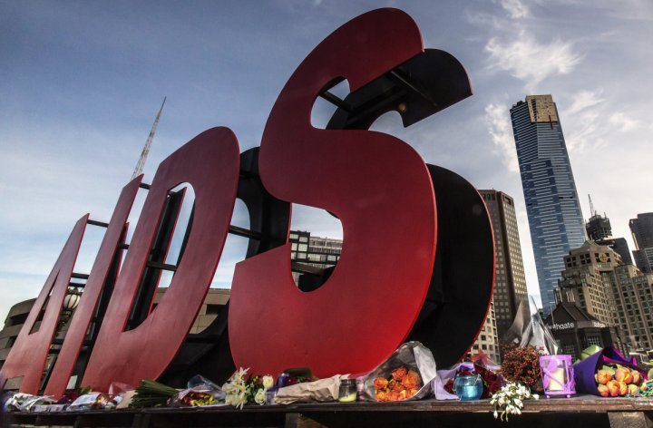 Flowers are laid as tributes to those killed in the Malaysia Airlines flight MH17, at the base of a large sign for the 20th International AIDS Conference in Melbourne July 20, 2014.