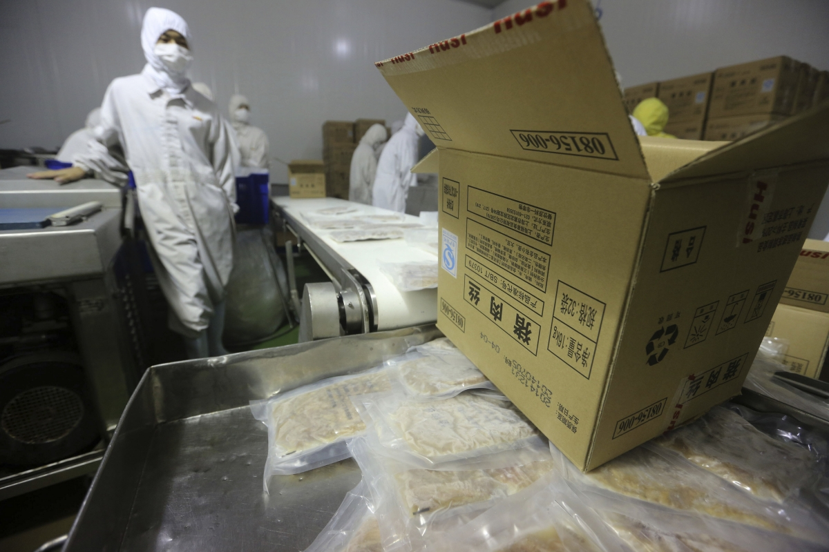 Employees work at a production line prior to a seizure conducted by officers from the Shanghai Food and Drug Administration, at the Husi Food factory in Shanghai, July 20, 201