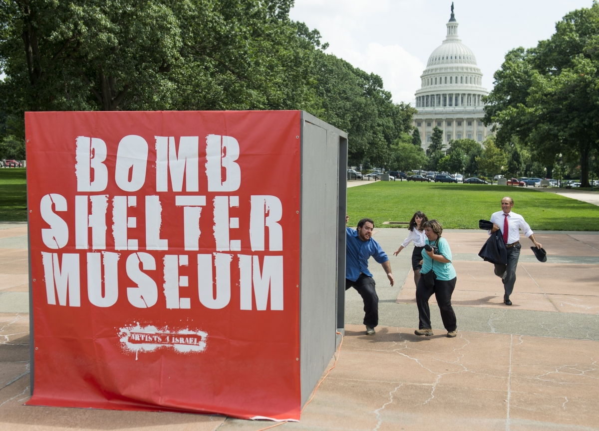 People run towards a mock bomb shelter during a simulated attack by Hamas rockets as part of a multimedia art exhibit called The Bomb Shelter Museum which is modeled after bomb shelters in Israel, near the US Capitol in Washington