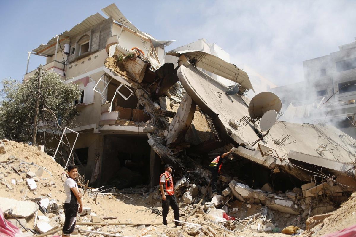 Palestinian rescue workers inspect house