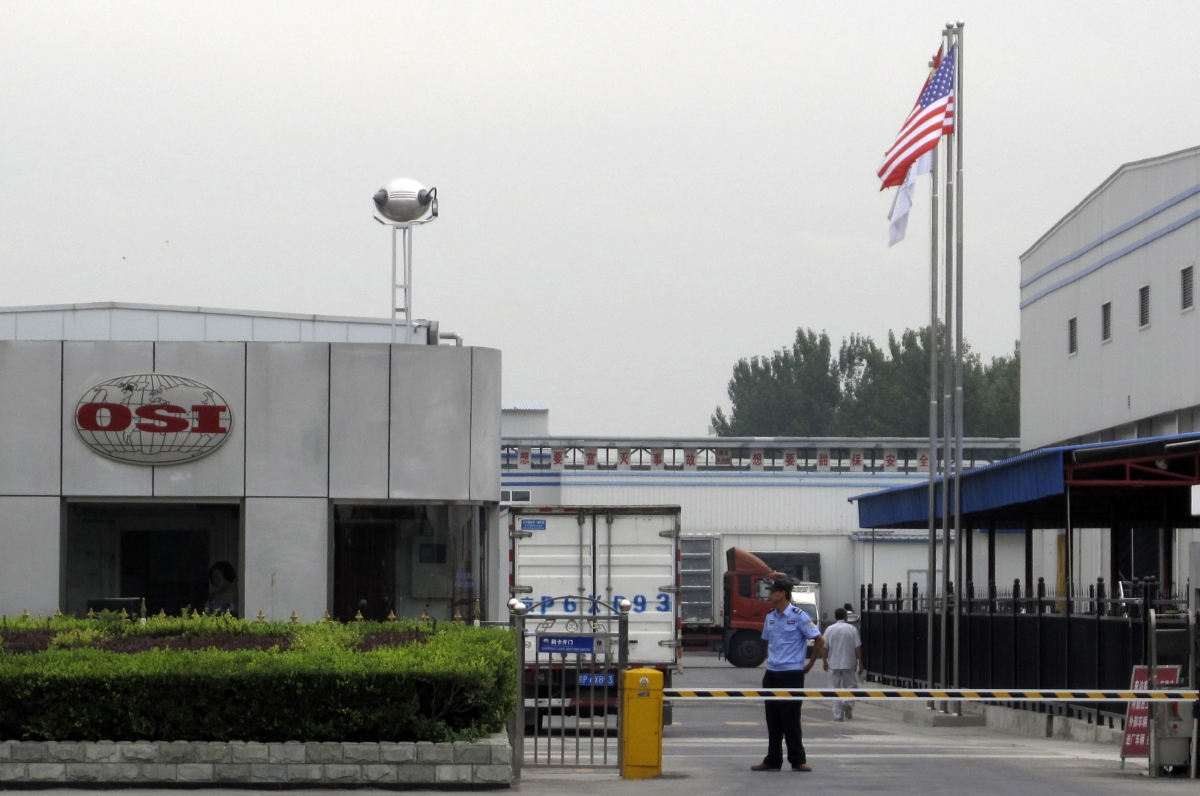 A security personnel stands guard in front of an OSI's food processing plants in Langfang, Hebei province