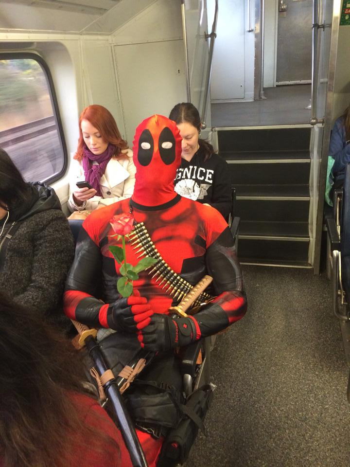 Rueben Rose as Deadpool, sitting in a train