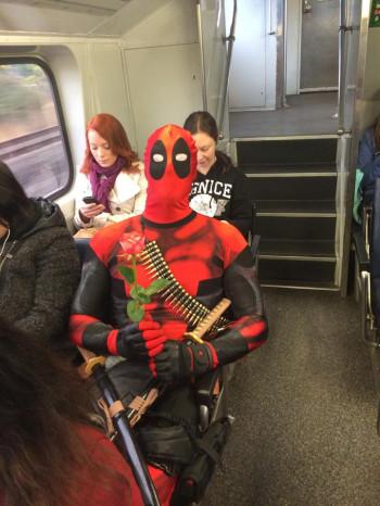 Rueben Rose as Deadpool, sitting in a train
