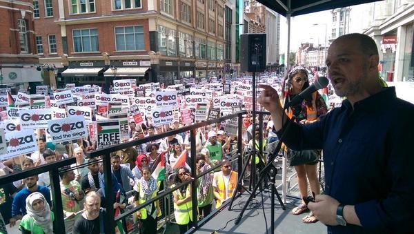 Spokesman for the Muslim Association in Britain addresses the crowds forming outside Israeli Embassy